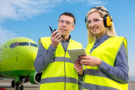 旅客機の前にラジオの立っていると航空機の労働者