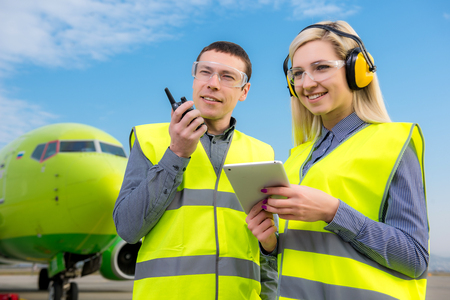 Aircraft workers with radio standing in front of a commercial airliner Stock Photo