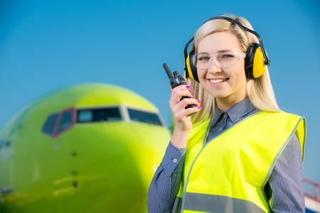 travailleur de l'aéronef avec la radio debout en face d'un avion de ligne commerciale Banque d'images