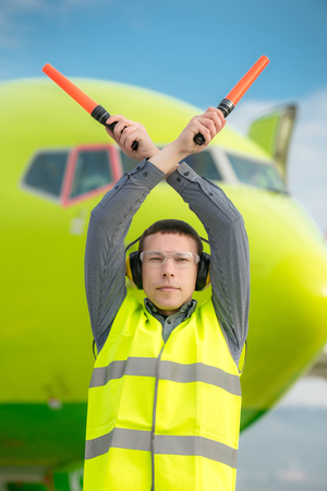 air traffic controller holding light signs at the airport Stock Photo