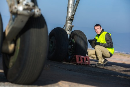 chassis: Male engineer checking airplanes chassis before flight