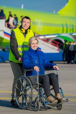 空港で障害者が車椅子を押すワーカー 写真素材