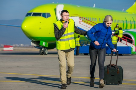 escorted: arrested woman escorted with an airport worker Stock Photo