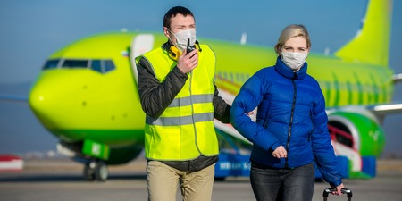tranfer: arrested woman escorted with an airport worker Stock Photo