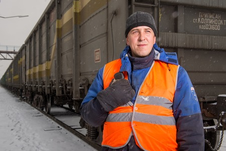 coordinating: RUSSIA - OCTOBER 19: Rail worker coordinating cargo loading to transport train on the tracks Editorial
