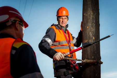 lineman: RUSSIA - OCTOBER 19: Electrician lineman repairman worker at climbing work on electric post power pole