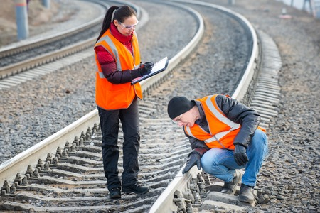 仕事をして鉄道の近くの男性と女性の鉄道労働者