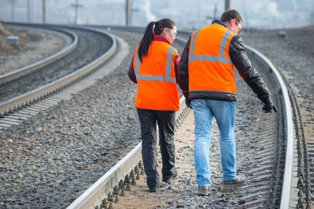 to maintain: Male and female railroad workers near railways doing their job