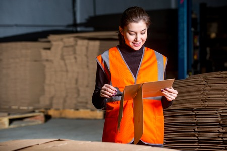 producing: Paper mill factory female worker with new box in her hand