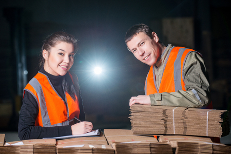 Workers with cardbord boxes checking its quality at the factory Stock Photo