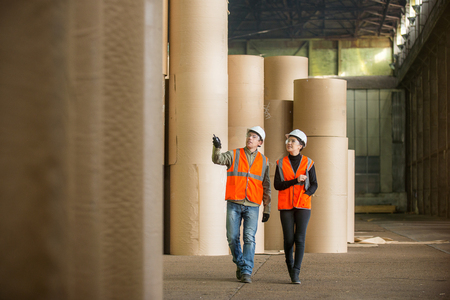 paper mill: Paper mill factory workers with giant paper rolls on the background
