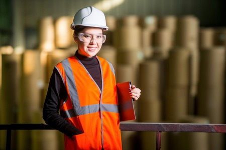 papermaking: Paper mill factory female worker with giant paper rolls on the background