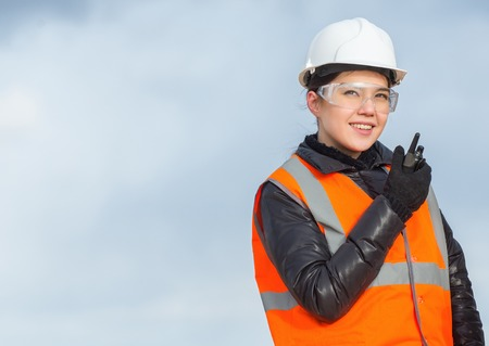 Beautiful female worker with radio at the factory
