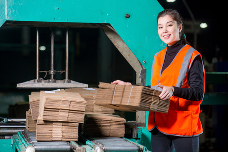 Worker with cardbord boxes near conveyor in distribution warehouse