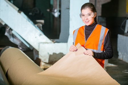 producing: Paper mill factory worker checking paper quality