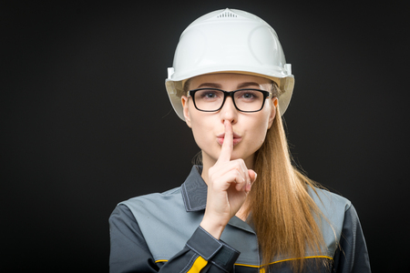 portrait of a young female worker on the black background Stock Photo