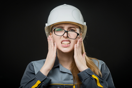 messed: portrait of a young female worker on the black background Stock Photo