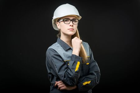 suggest: portrait of a young female worker on the black background Stock Photo