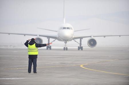 Aéroport travailleur diriger un avion comme il est arrivé Banque d'images - 68640177