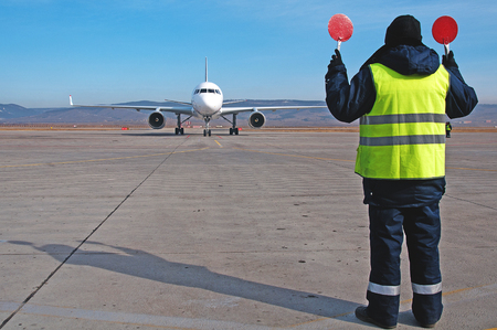 Airport worker directing airplane at an airport