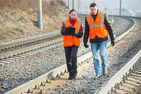 Male and female railroad workers near railways doing their job