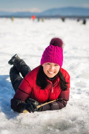 Woman ice-fishing in the winter