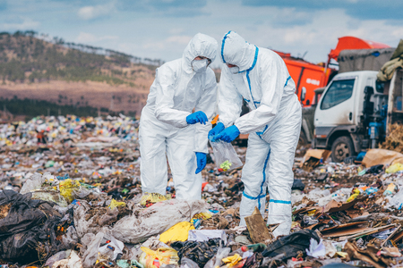dirt: Recycling workers researching on the landfill Stock Photo