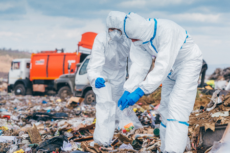 Recycling workers researching on the landfill Standard-Bild
