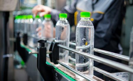 Transportband van een waterfabriek. Flessen gevuld met zuiver water.