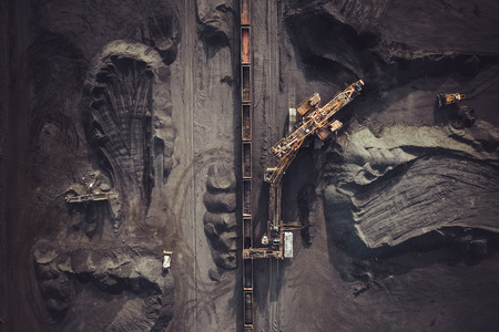 Coal mining. Aerial view. Excavator loading train cargos