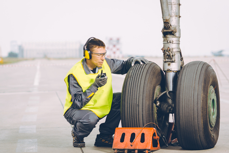 airport worker mechanic service maintenance chassis tire Stock Photo