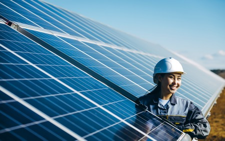 A female technician at a solar power station Stock Photo