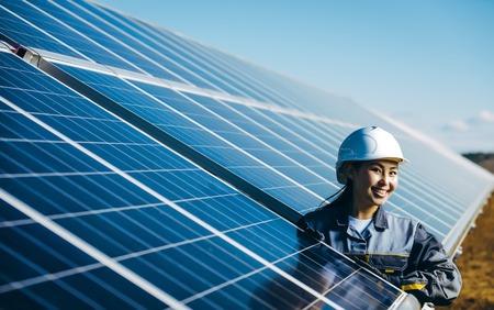 A female technician at a solar power station Archivio Fotografico