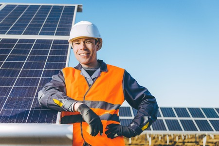electricity export: A man in front of a solar power station green electricity panel background
