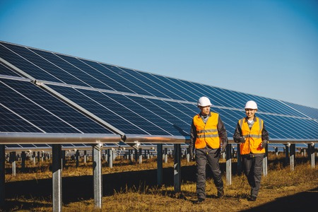 A man and a woman walking at the solar panel of a solar power station Stock Photo