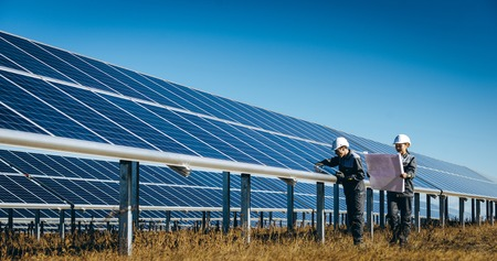 A man and a woman working at the solar panel of a solar power station Archivio Fotografico