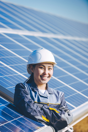electricity export: A female technician at a solar power station Stock Photo