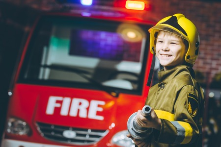 A boy wearing a firefighter uniform smiling