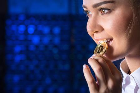A woman biting a bitcoin Stock Photo