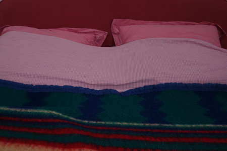 Vintage bed with pink vichy gingham sheets and wool blanket