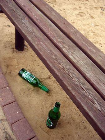 emptied: Emptied beer bottles left under a playground bench, near children�s sandbox