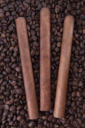 Three cigar on coffee beans background photo
