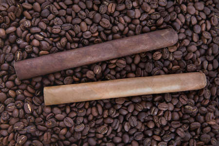 two cigar on coffee beans background photo