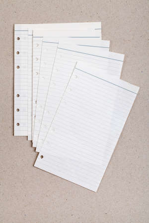 busines: clean sheet of lined notebook on a gray cardboard