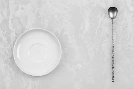 delftware: pulito piatto bianco e un vecchio cucchiaio d'argento su uno sfondo bianco