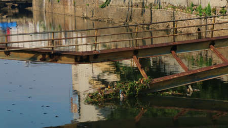 The old and broken bridge over the river in the morning. Archivio Fotografico