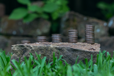 Saving money represented by 5 stacks of coins representing growth outside with natural background.
