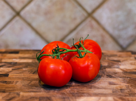 Tomatos on a vine sitting on a wood block with kitchen backsplash in background. 版權商用圖片