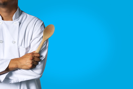 Chef with wooden spoon background with space for text