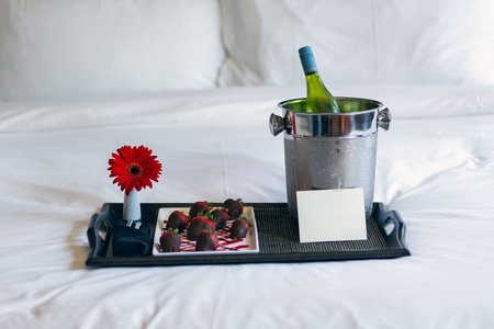 Chocolate covered strawberries on tray with wine and flower and blank card for added text sitting on a bed 版權商用圖片